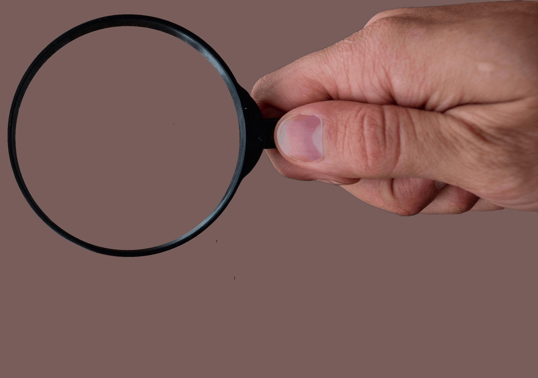 Hand hält schwarze Lupe - Agentur für Suchmaschinenoptimierung aus Köln